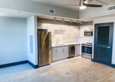 Silver Lacquer Kitchen Cabinets with Chrome Pulls at Merchants Plaza's Downtown Mobile Apartments
