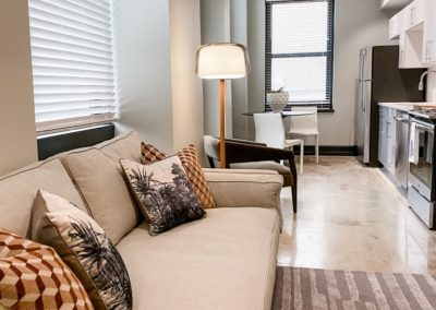 Living Room With a Couch and Pillows in an Apartment at Merchants Plaza